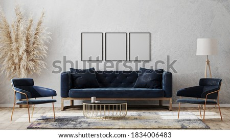 Three blank poster frames on gray wall mockup in modern luxury interior design with dark blue sofa, armchairs near cofee table, fancy rug on wooden floor, 3d rendering