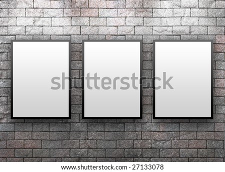 Three blank, white canvas frames are hanging on a brick wall. Light is shining down on them.