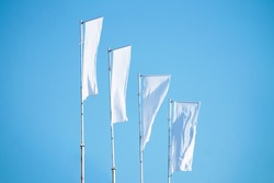 Three blank white flags on flagpoles against cloudy blue sky with perspective, corporate flag mockup to ad logo, text or symbol, company identity flag template with copy space