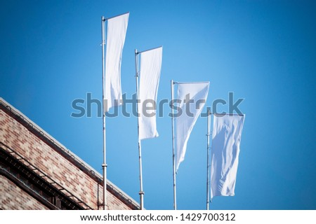 Three blank white flags on flagpoles against cloudy blue sky with perspective, corporate flag mockup to ad logo, text or symbol, company identity flag template with copy space #1429700312