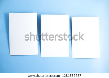 Three blanks white postcards / flyers / invitations mock-up on blue background, copy space