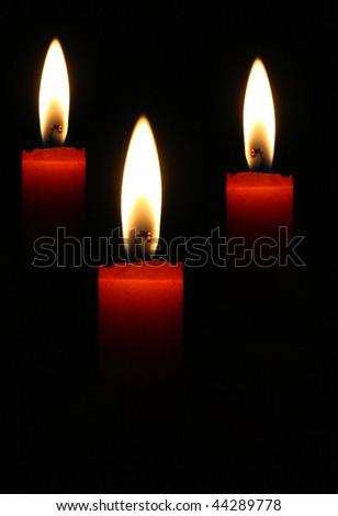Three blazing candles on a black background