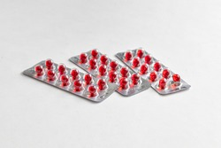 Three blister packs with round red vitamin capsules, covered with gelatin, on a light background