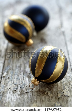 three blue christmas ornaments made of blue and gold glass on a wooden plank.