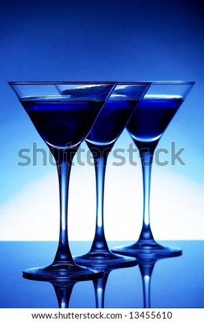Three blue cocktails on blue background