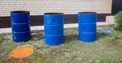 Three blue metal barrels at a construction site.
