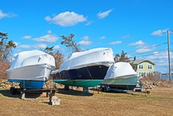 Three boats are stored for the winter in Fairhaven, Massachusetts, out of the water and on blocks with shrink-wrap style covers to protect them from the elements.