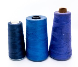 Three bobbin threads isolated on white background. Close up of spools of blue shades of sewing thread. Thread is a type of yarn used for sewing.