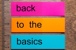 Three bookmark stickers with the phrase back to the basics on a dark natural wooden table