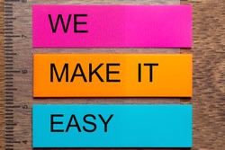Three bookmark stickers with the words WE MAKE IT EASY, on a dark natural wooden table