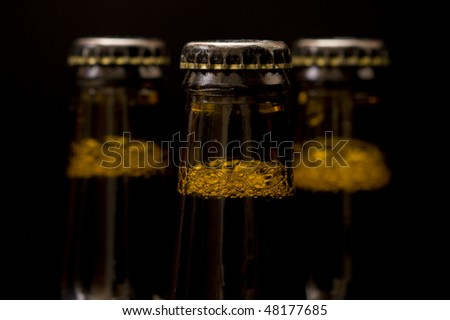 Three bottles beer isolated on black - Focus on the first bottle