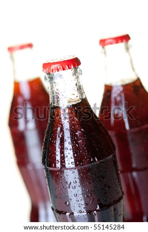 Three bottles of cold cola with water drops. Closeup, small DOF