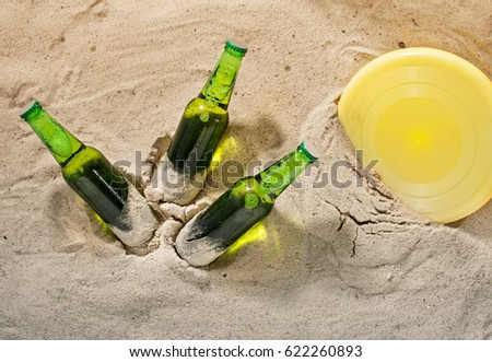 Three bottles of cold lager beer with object for beach games on sand, top view. Summer background