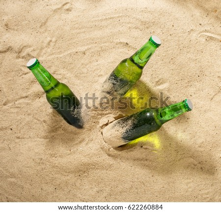Three bottles of cold light beer on sand, top view. Summer background