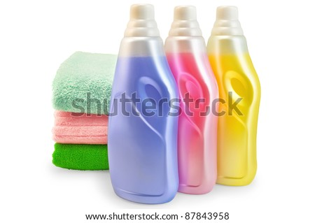 Three bottles of fabric softener pink, yellow and lilac, three of towels isolated on white background