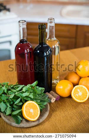 Three bottles of wine: white, rose and red, empty glasses and fruits on the kitchen table in a kitchen interior, closeup