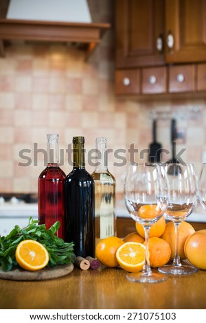 Three bottles of wine: white, rose and red, empty glasses and fruits on the kitchen table in a home kitchen interior
