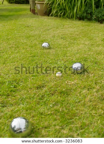 Three boules and jack on a lawn