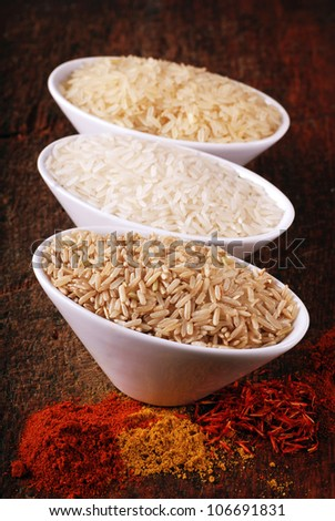 Three bowls with different types of rice: wild rice, white (jasmine) rice, brown rice,  and indian spices on wood board. Selective focus.