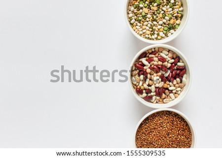 Three bows with variety of legume grains buckwheat, white red beans arranged on the right of image. Photo with copy blank space.