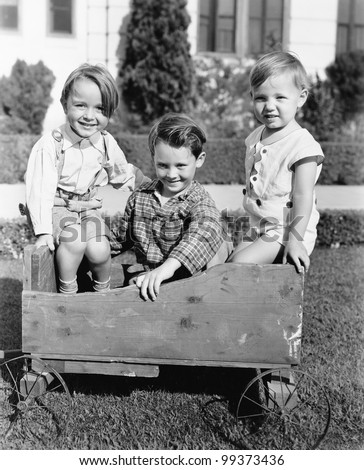 Three boys sitting in a push cart and smiling Zdjęcia stock ©