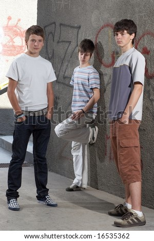 Three boys standing beside a wall