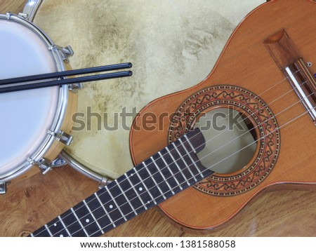 Three Brazilian musical instruments: cavaquinho, pandeiro (tambourine) and tamborim with drumstick on a wooden surface. The instruments are widely used to accompany samba music.