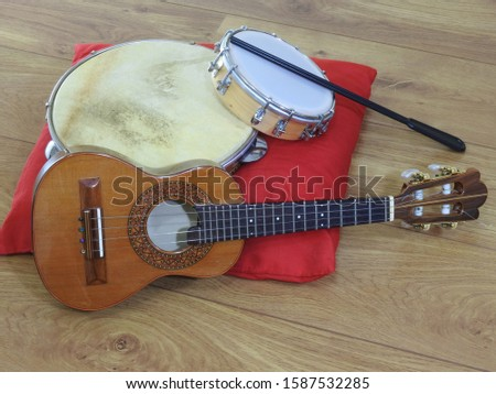 Three Brazilian musical instruments: cavaquinho, pandeiro (tambourine) and tamborim with drumstick on a red pillow on a wooden surface. The instruments are widely used to accompany samba music.