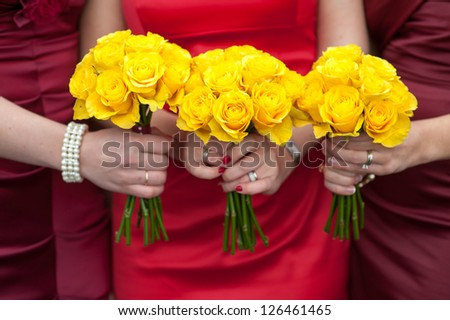 three bridesmaids holding wedding bouquets of yellow roses