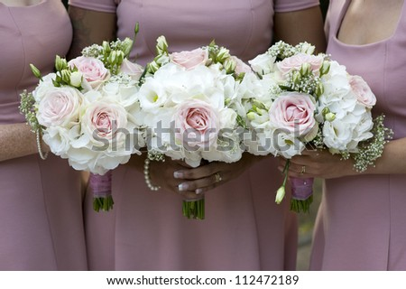 three bridesmaids in pink dresses holding wedding bouquets of white roses