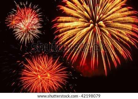 Three bright bursts of fireworks, with gold predominating