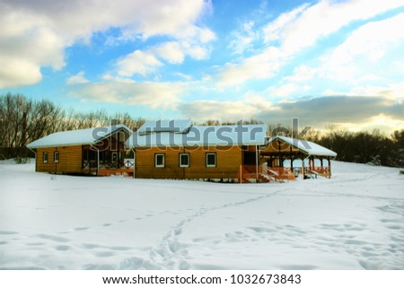 Three bright yellow houses for rest in the middle of a snowy meadow in the forest during the daytime winter.Moscow, Russia