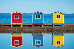 Three brightly colored storage sheds, red, blue and yellow at the ocean's edge. There's a little pond in front of the buildings which is reflecting in the water. The sky is blue in the background.