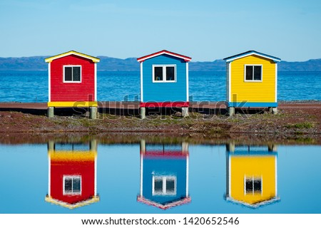 Three brightly colored storage sheds, red, blue and yellow at the ocean's edge. There's a little pond in front of the buildings which is reflecting in the water. The sky is blue in the background.  #1420652546