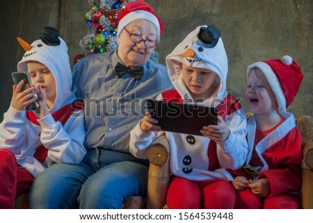 Three brothers in xmas clothes play with tablet and smartphone. Granny sits next to her grandsons and looks at their entertainment. Beautiful elderly woman with gray hair and wrinkles. Kids love mom