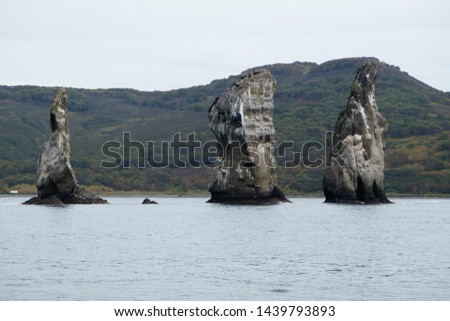 Three Brothers rocks in Pacific ocean in cloudy day, Kamchatka peninsula