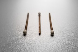 Three brown and white matches. White background, some matchbooks. Wooden matchsticks. Studio light