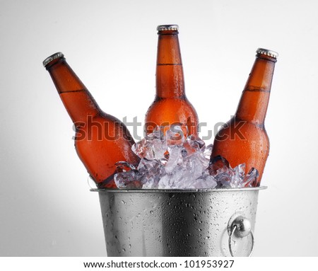 Three brown beer bottles in ice bucket with condensation