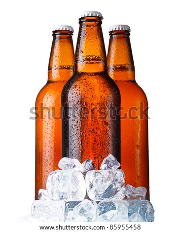 Three brown bottles of beer with ice isolated on white background