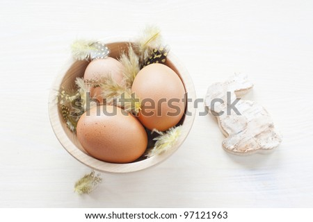 three brown chicken eggs on the feathers in a wooden bowl on a wooden table, close to the cut of birch bunny