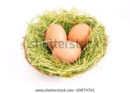 Three brown hen's eggs in the grassy nest isolated on white