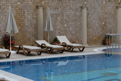 Three brown sunbeds with biege matresses and two striped umbrellas against mosaic wall with columns