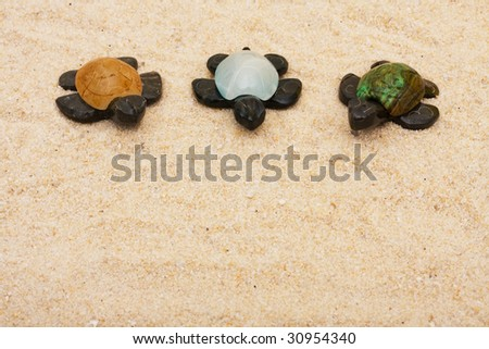 Three brown turtles with colourful shells sitting on a sand background, three turtles