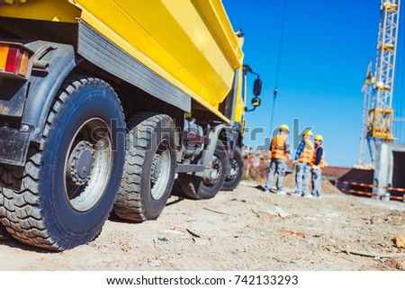 Three builders in uniform standing near a big yellow tip truck at construction site