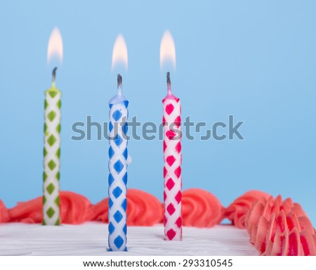 Three burning birthday candles on a cake with blue background