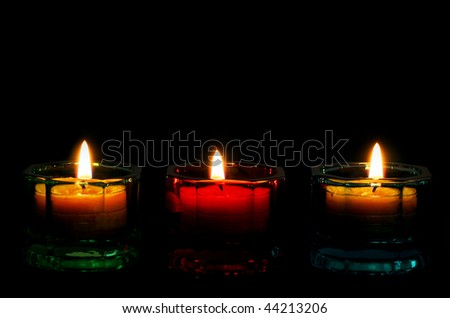 Three burning candles form a bottom border on black, with copy space.