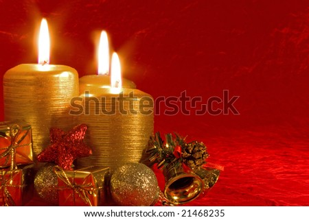Three burning candles in a Christmas setting with seasonal decorations