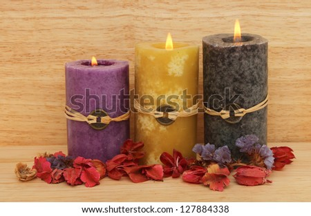 Three burning Feng Shui candles and potpourri against a wooden background