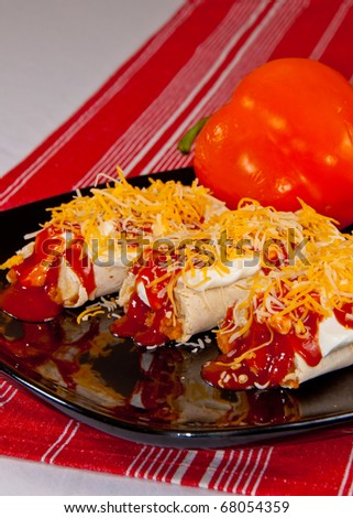 Three Burritos covered in Sour Cream, Enchilada Sauce, and Shredded Cheese on a Black Plate on a Red Cloth with an Orange Bell Pepper in the Background.