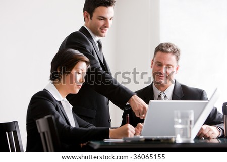 Three business associates working together, with one associate pointing at laptop